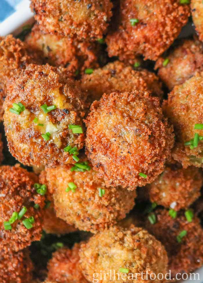 Close-up of fried potato balls sprinkled with chives.