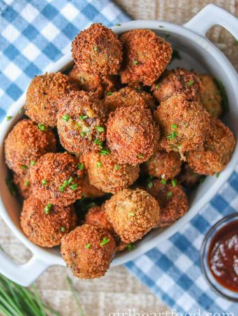Dish of fried mashed potato balls that have been sprinkled with chopped chives.