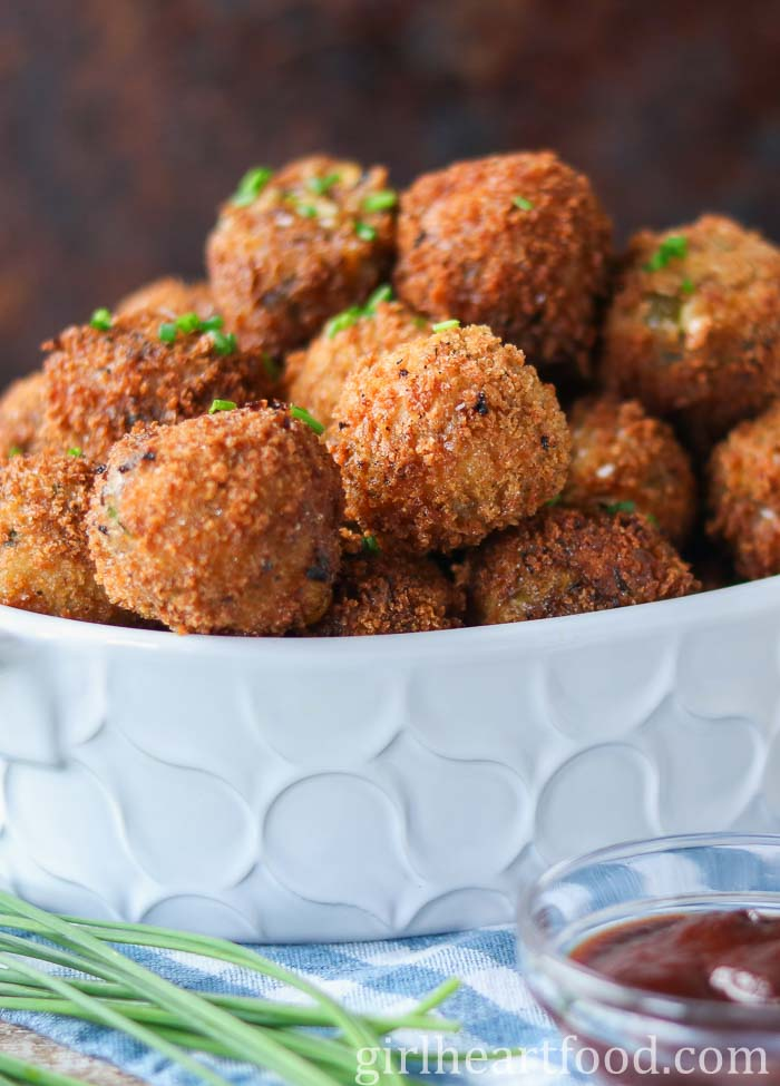 Dish of potato cheese balls garnished with chives.