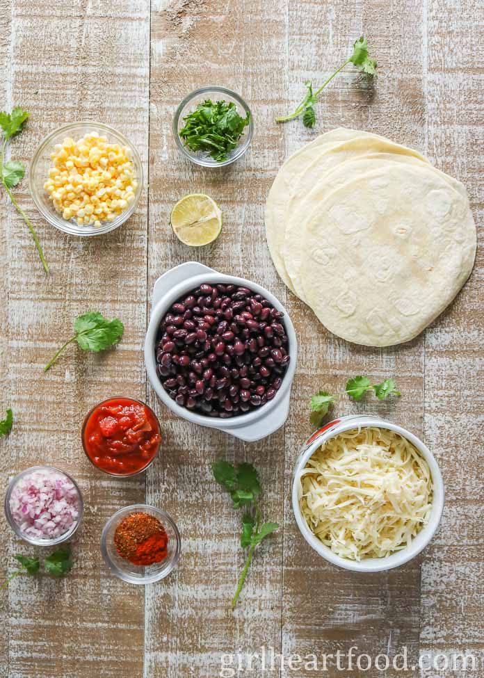 Ingredients for a vegetarian quesadilla recipe on a wooden board.