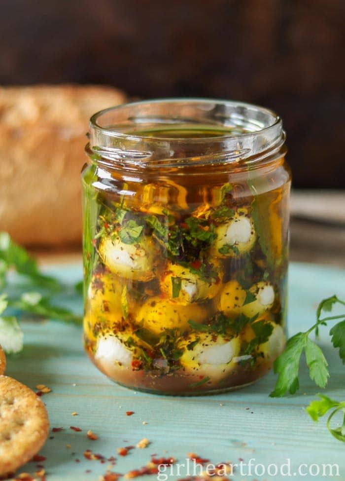 Jar of marinated mozzarella balls next to some fresh parsley.