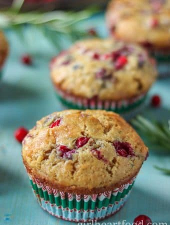 Partridgeberry muffins on a blue platter next to some partridgeberries and fresh rosemary.
