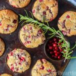 Partridgeberry muffins in a muffin tin alongside some Newfoundland partridgeberries and a sprig of rosemary.