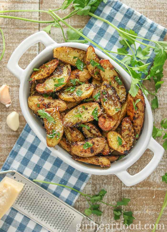 White dish of a fingerling potato recipe garnished with parmesan and parsley.