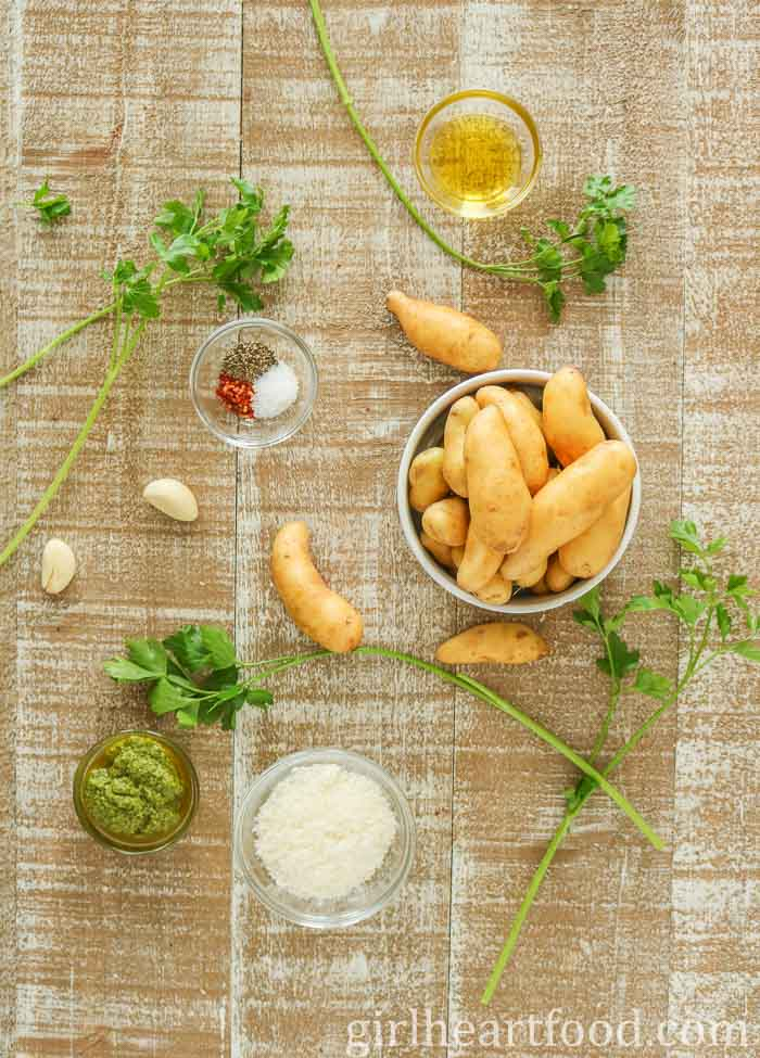 Ingredients for oven roasted fingerling potatoes with pesto on a wooden board.