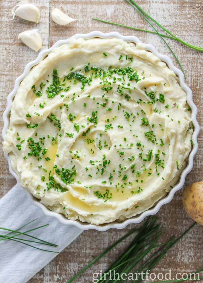 Dish of garlic mashed potatoes garnished with chives and melted butter.