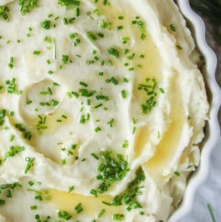 White round casserole of roasted garlic mashed potatoes drizzled with melted butter and sprinkled with chives.