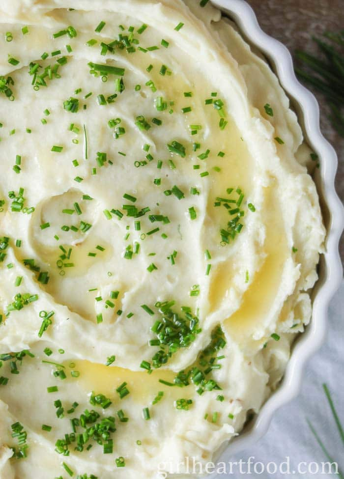 Close-up of a dish of creamy garlic mashed potatoes with melted butter and chives on top.