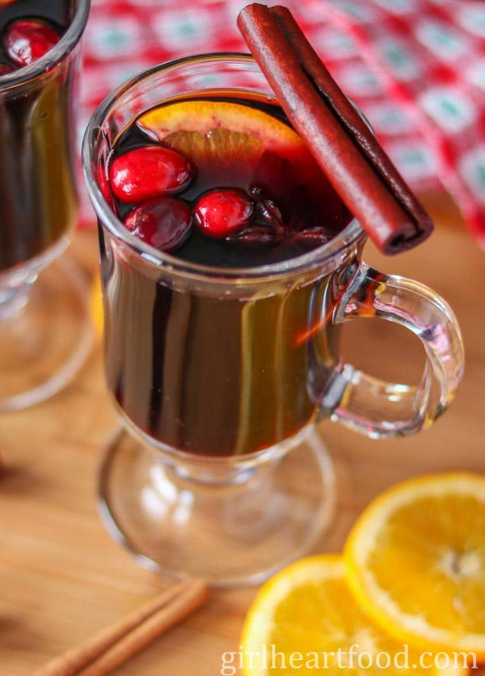 Glass of hot wine garnished with cranberries, orange, star anise and a cinnamon stick.