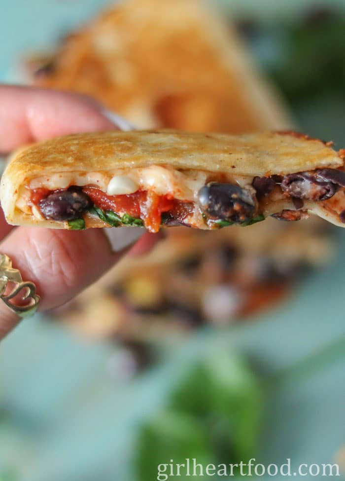 Holding a black bean and cheese quesadilla.