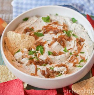 Bowl of homemade onion dip garnished with caramelized onions and parsley.