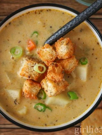 Bowl of celery root soup garnished with croutons and green onion.