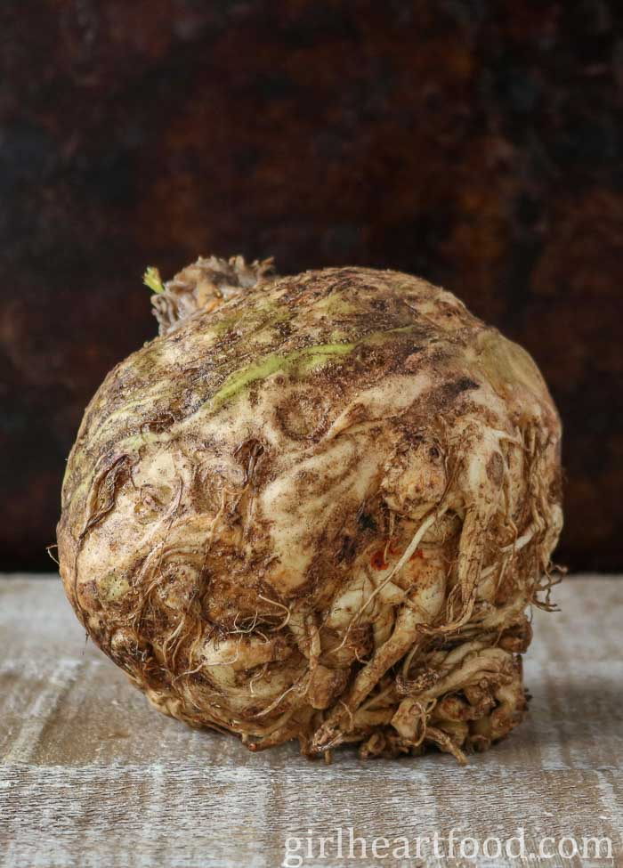 A bulb of celery root on a wooden board.