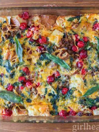 Breakfast strata in a glass casserole dish topped with crispy sage.