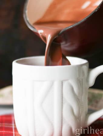 Pouring homemade hot chocolate from a pot to a white mug.