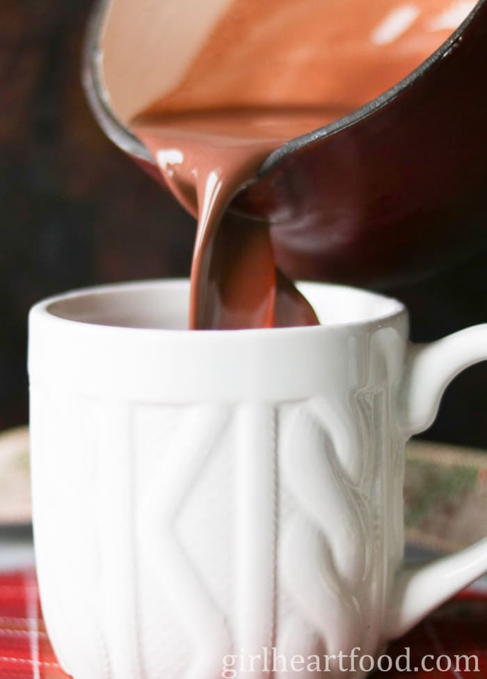 Pouring dark hot chocolate from a saucepan to a white mug.