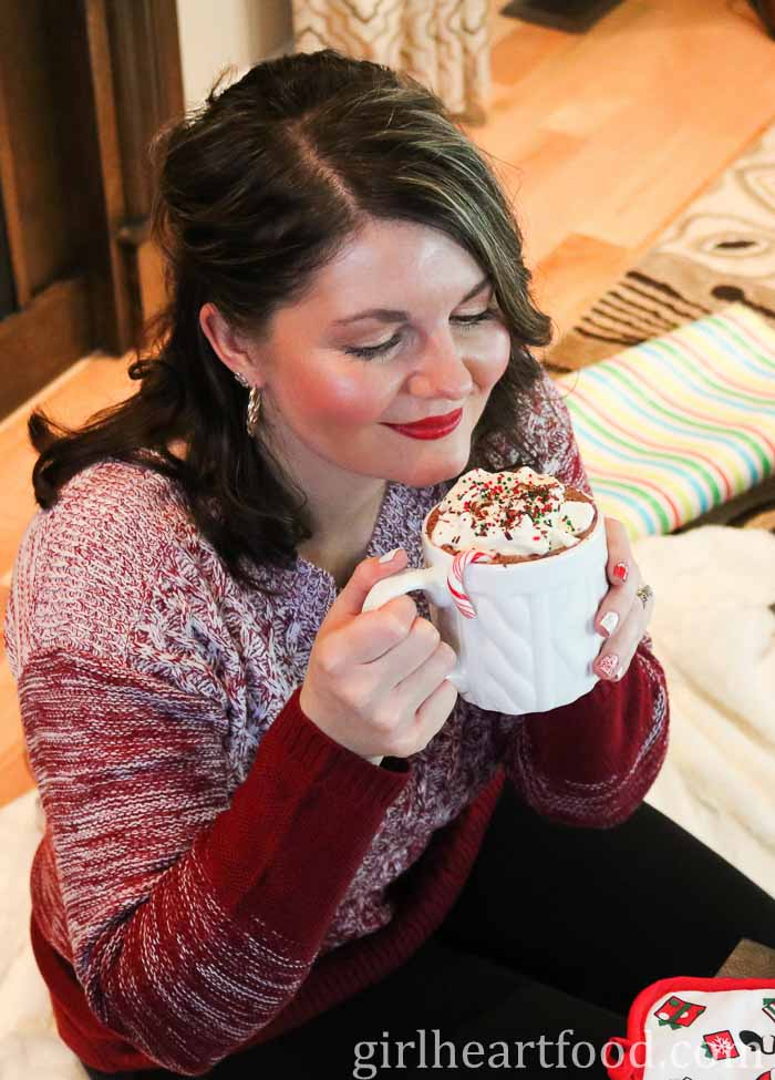 Woman holding a mug of a hot chocolate drink, looking down at it.