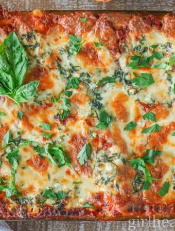 Large pan of meat lasagna garnished with fresh parsley.