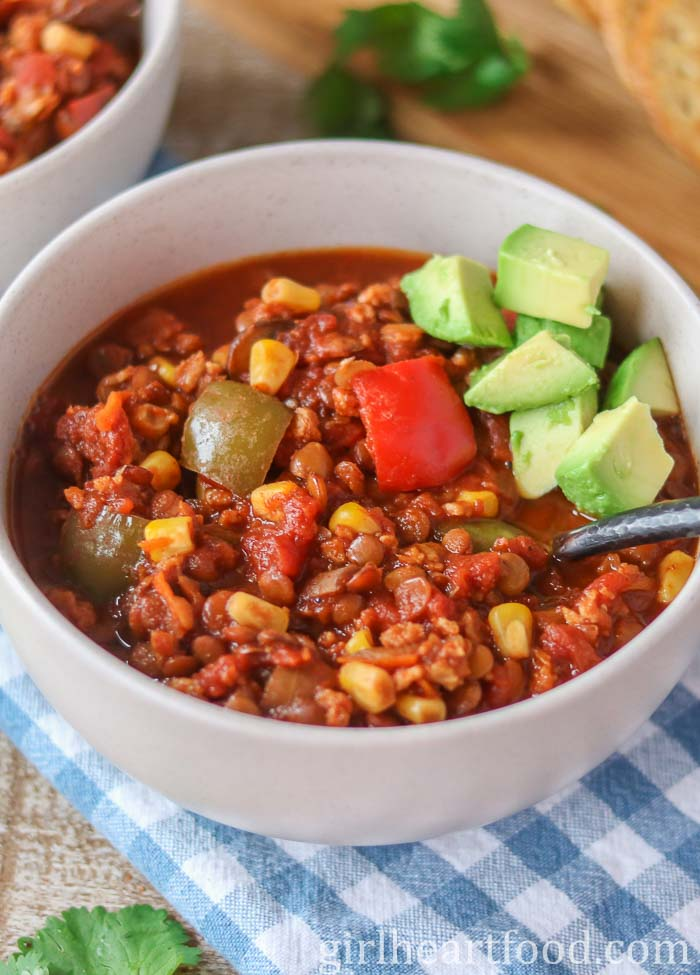 Bowl of lentil chili topped with diced avocado.