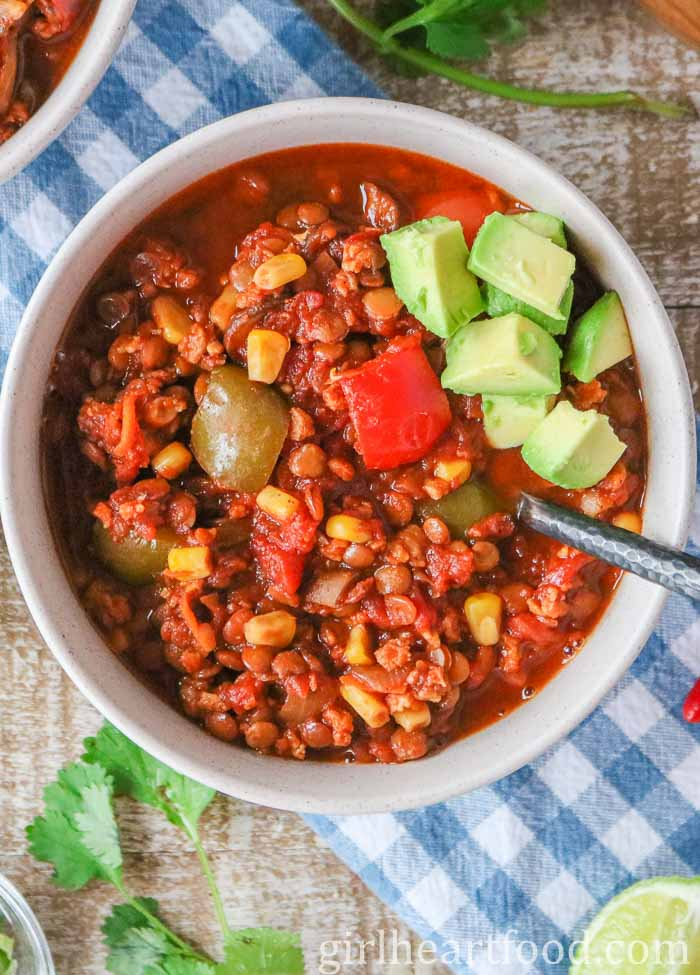 Overhead shot of a bowl of lentil chili topped with diced avocado and a spoon dunked into the chili.
