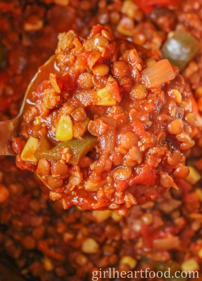 A large ladle of meatless chili from a pot.