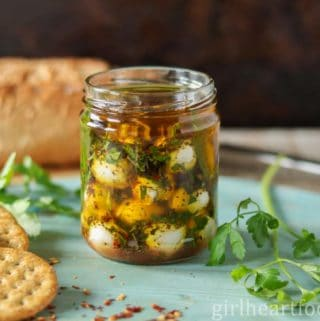 Jar of marinated mozzarella balls next to crackers, parsley and loaf of bread.