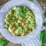 Bowl of a simple guacamole recipe garnished with fresh cilantro.