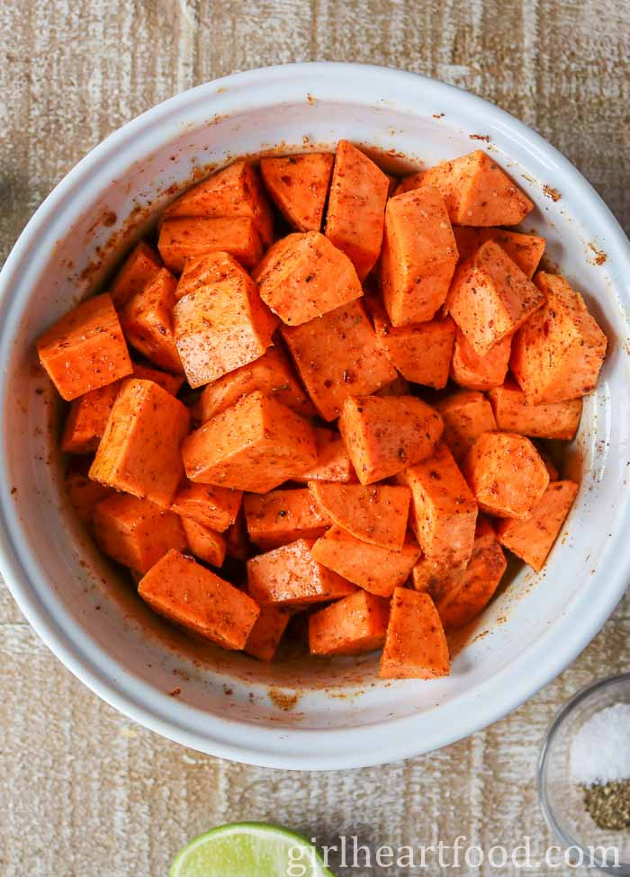 Spiced sweet potato chunks in a bowl before being roasted.