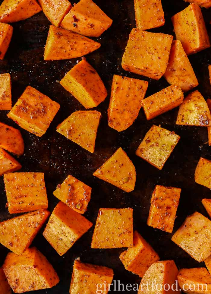 Chunks of spiced sweet potato on a sheet pan before being cooked.