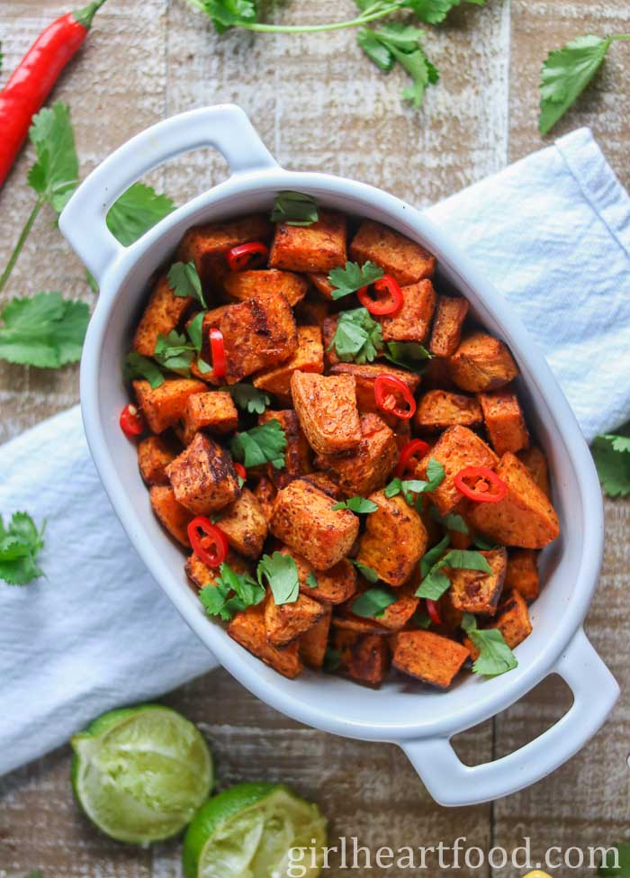 Dish of roasted sweet potato chunks garnished with cilantro and chili pepper.