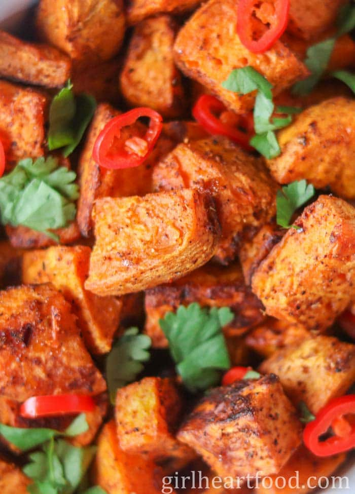 Close-up of roasted sweet potato chunks garnished with cilantro and chili pepper.