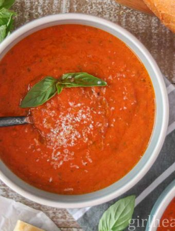 Bowl of tomato soup made with fresh tomatoes and garnished with basil and parmesan.