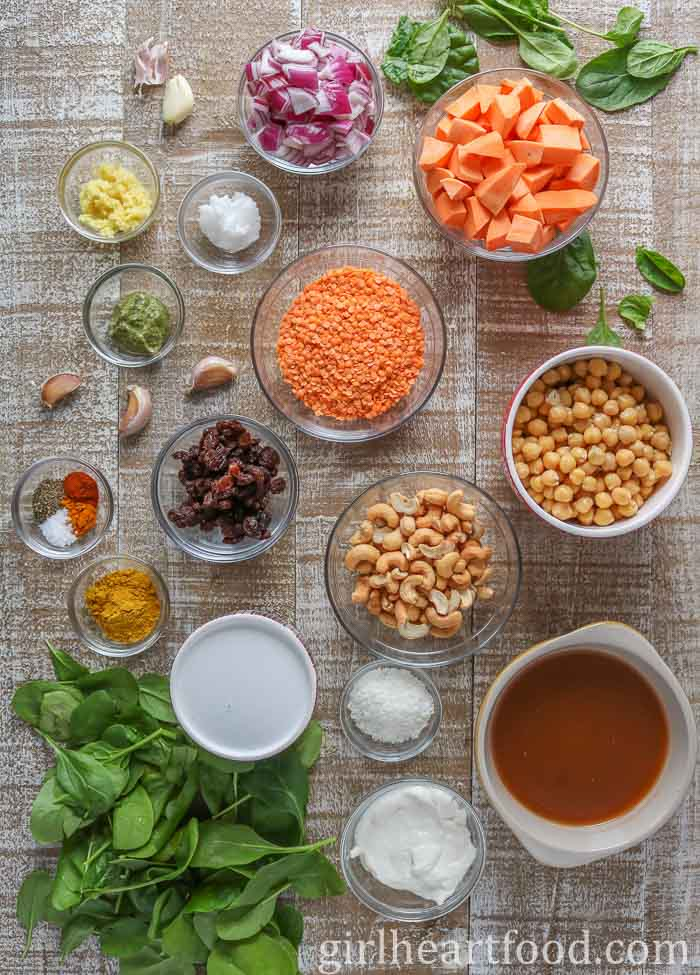 Ingredients for a lentil and chickpea curry recipe on a wooden board.