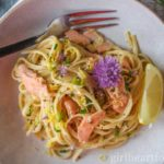 Bowl of creamy smoked salmon pasta garnished with a fresh chive flower and lemon wedge.
