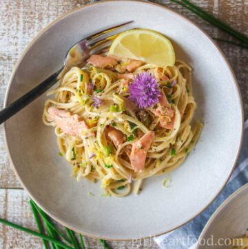 Overhead shot of a bowl of creamy smoked salmon pasta garnished with a chive flower, lemon, and chives.