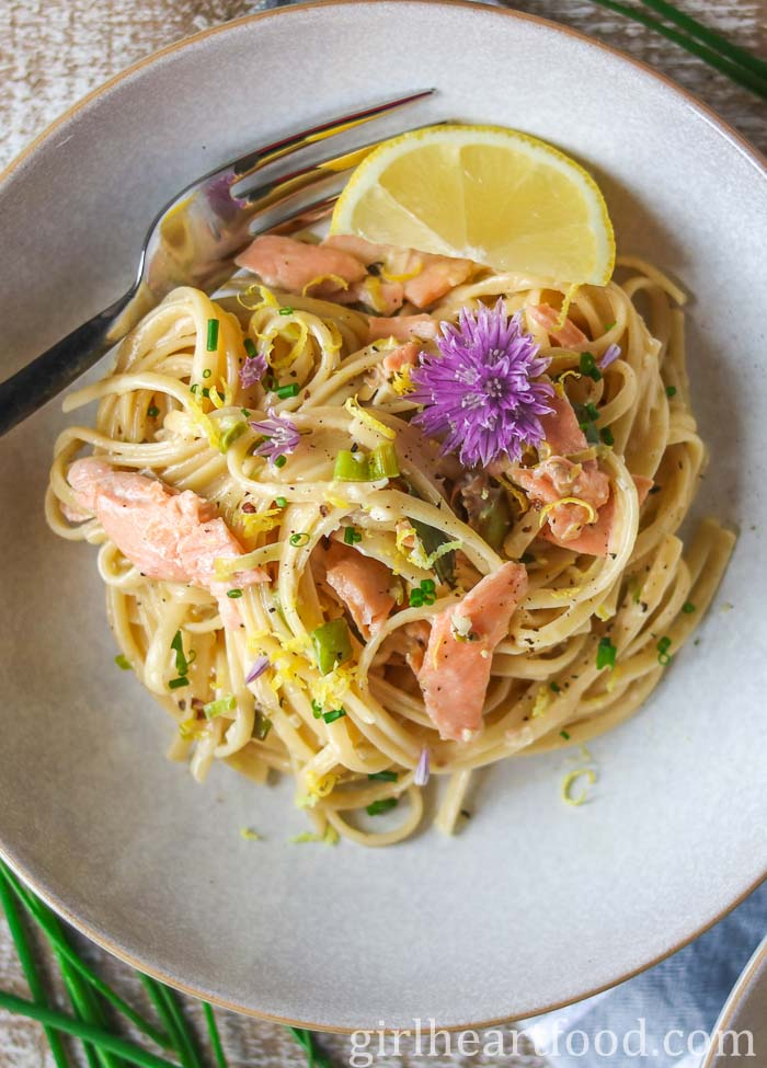 Bowl of creamy smoked salmon pasta garnished with a chive flower.