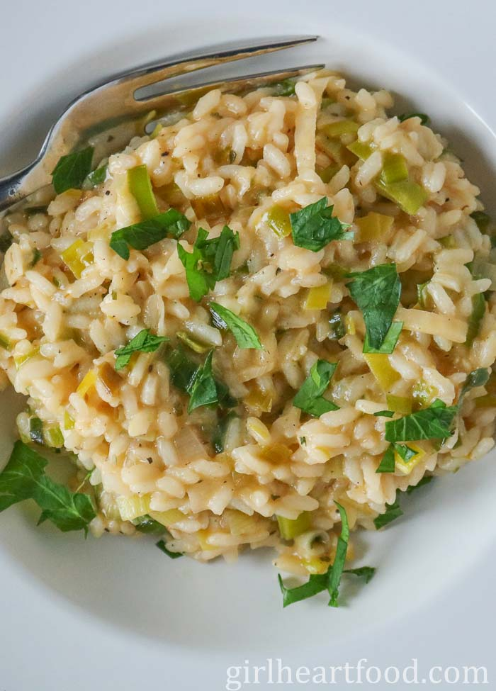 Close up of a white bowl of homemade risotto made with leeks and garnished with fresh parsley.