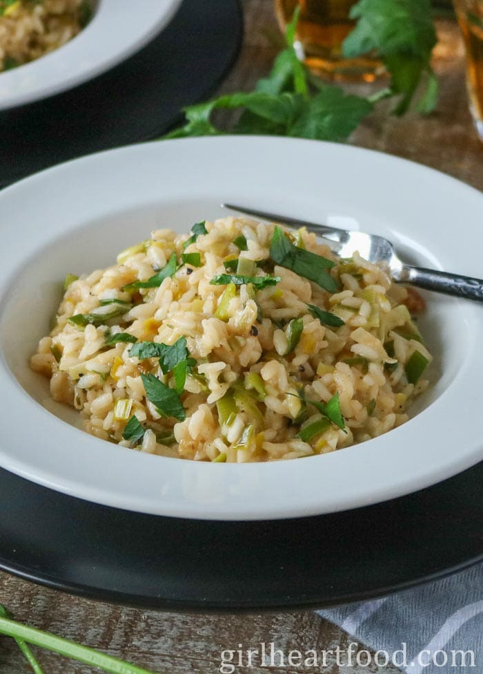 Round white bowl of a simple risotto with a fork resting on bowl.