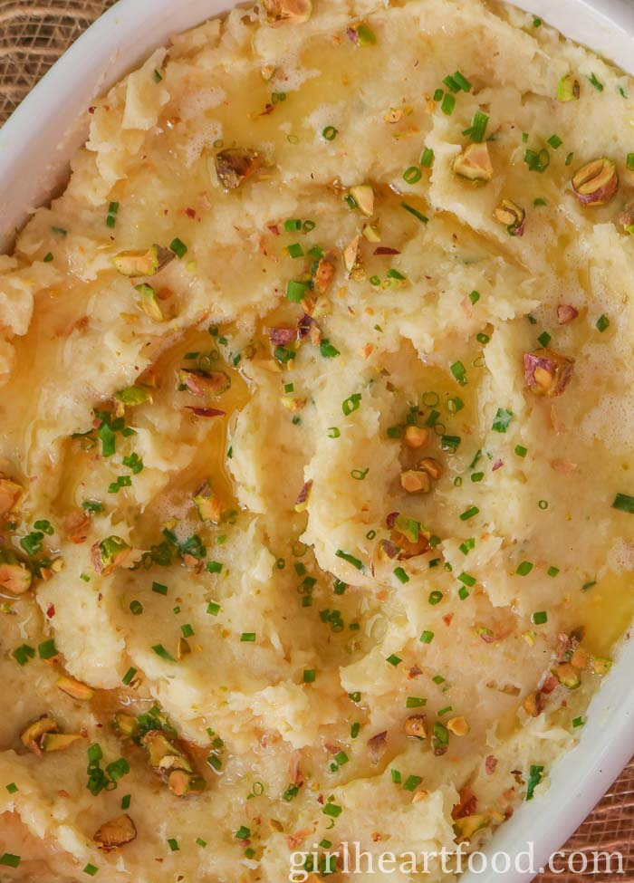 Close up of a dish of mashed parsnip garnished with chives and pistachios.