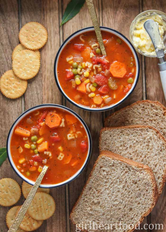 Two bowls of alphabet vegetable soup next to crackers, bread and a dish of butter.