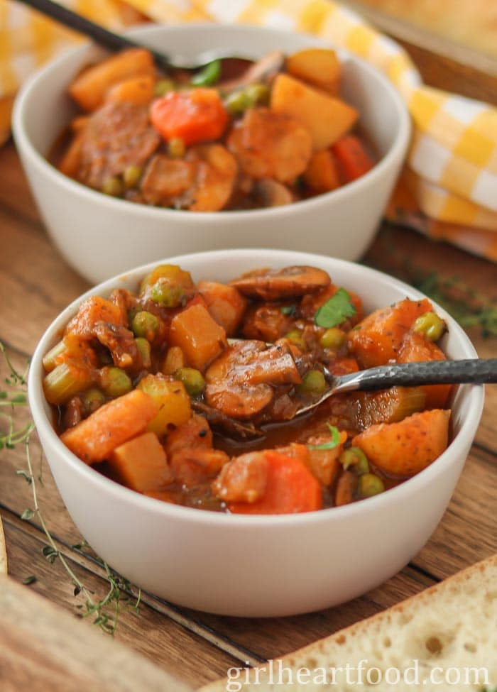 Two white bowls of veg stew with spoons in the bowls.