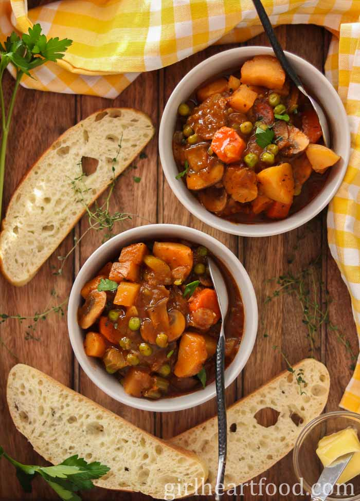 Two bowls of vegetable stew, each with a spoon resting in it, alongside slices of bread.