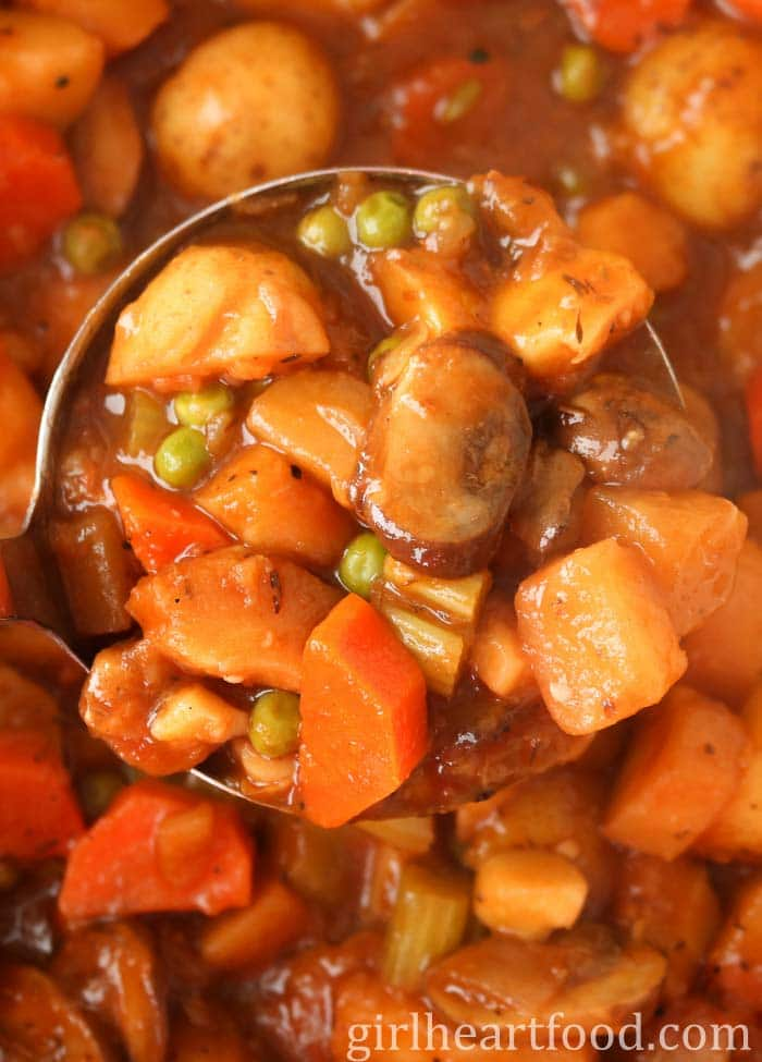 A ladle of winter vegetable stew from a pot.
