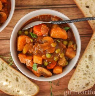 White bowl of veggie stew alongside some slices of bread.