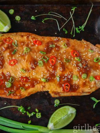 Fillet of baked arctic char on a sheet pan garnished with sliced chili, green onion and sesame seeds.