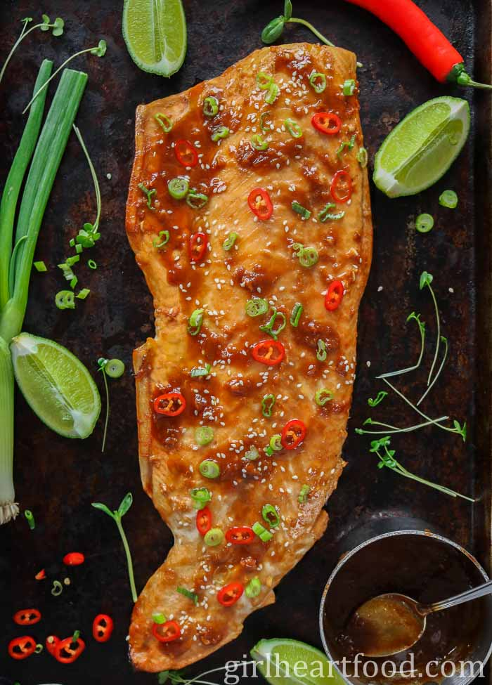 Fillet of cooked arctic char on a sheet pan garnished with chili and sesame seeds.