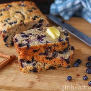 A blueberry banana bread with slices cut out of it stacked on top of each other with a dab of butter on top.