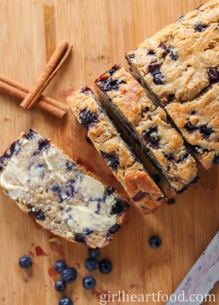 Sliced blueberry loaf next to cinnamon sticks and blueberries.