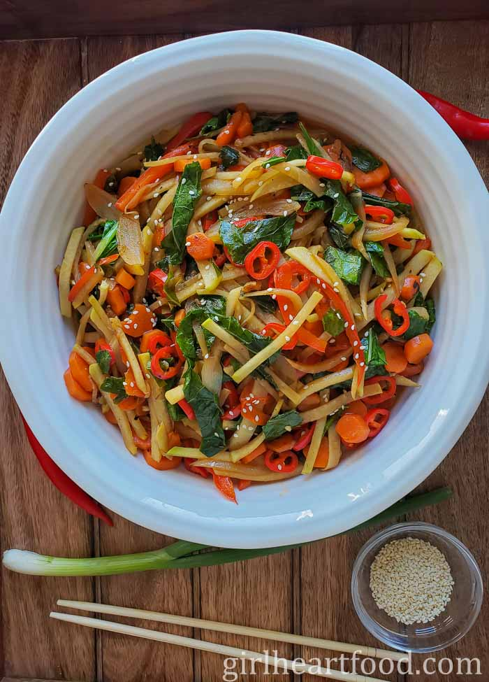 Large white dish of stir fried vegetables alongside green onion, chili, sesame seeds and chop sticks.