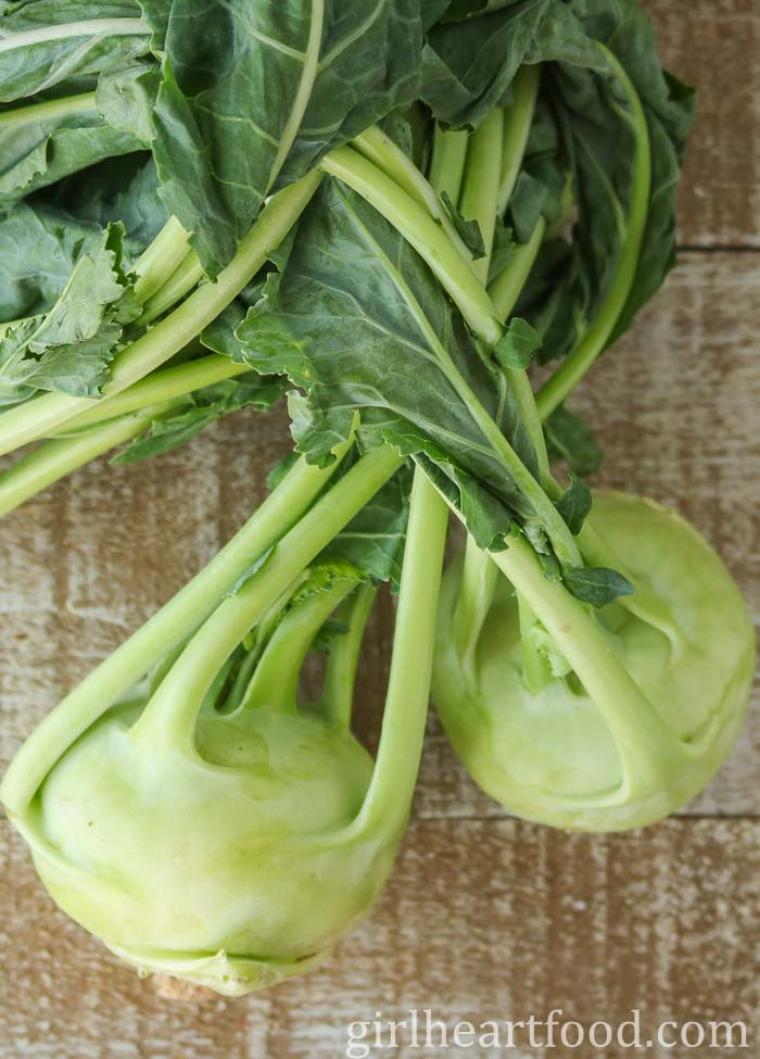 Kohlrabi with greens on a wooden board.